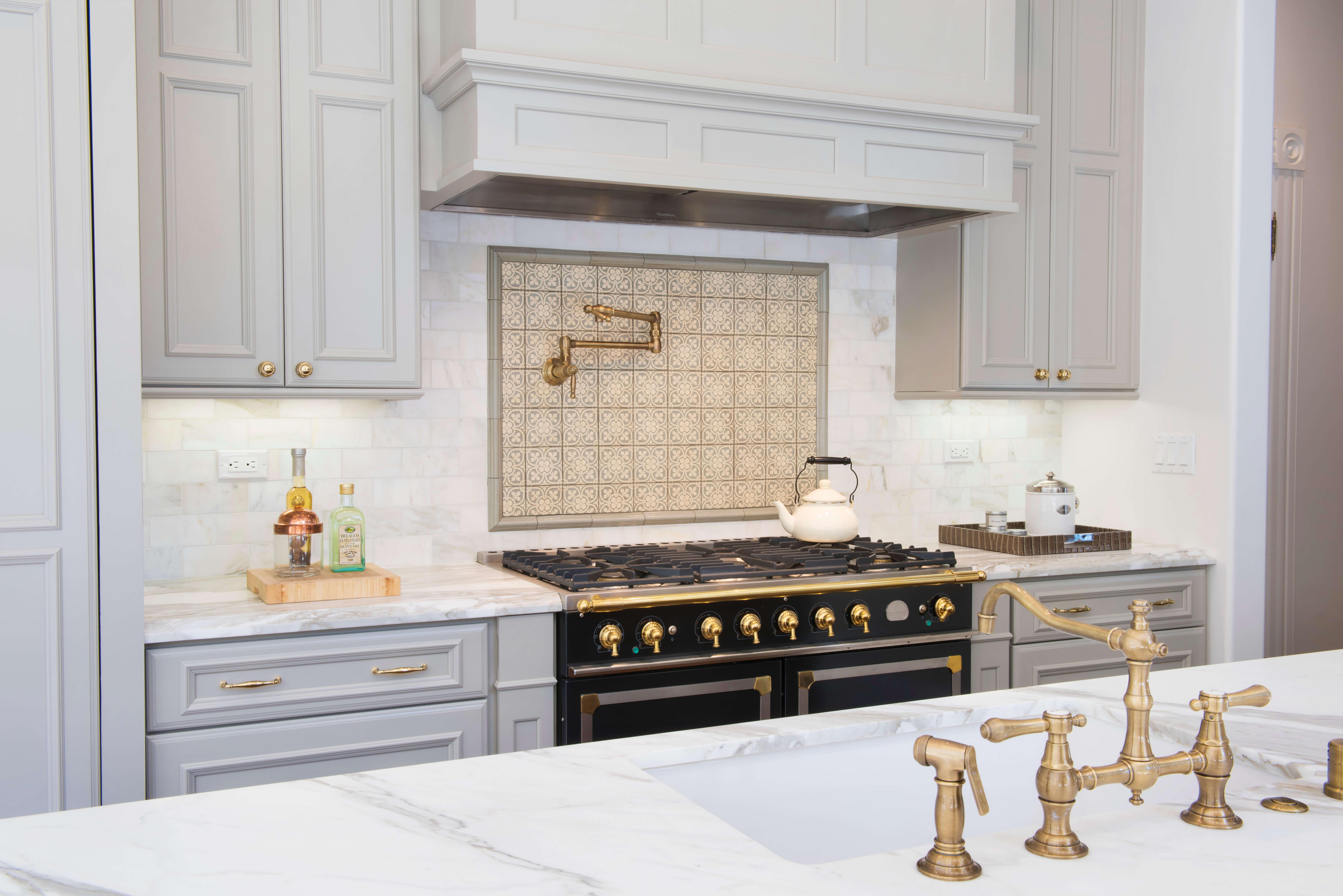 This elegant Dura Supreme kitchen adorned with brassy gold accents was designed by Joyce Van Den Dungen Bille of Gilmans Kitchens and Baths, California.
