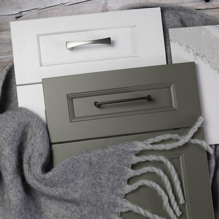 Cabinet door styles in a white painted oak and a dark sage green from Dura Supreme Cabinetry.