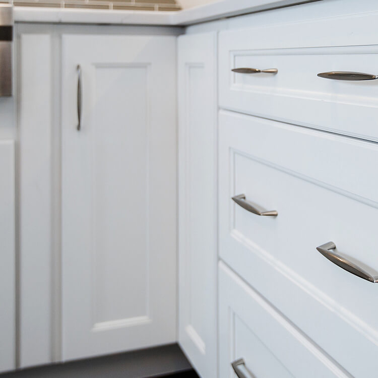 Corner Base Cabinets That Maximize Your Kitchen Storage Space. White cabinets showing a close up of a corner cabinet.