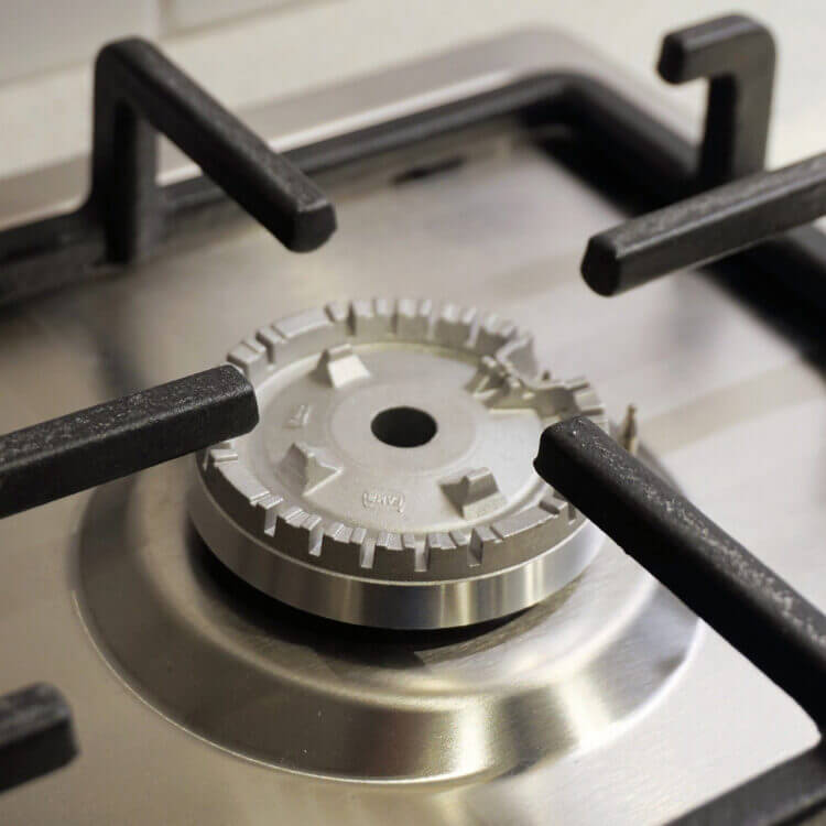 A close up of a gas burner on a stove top. How to plan a kitchen remodel and new kitchen appliances.